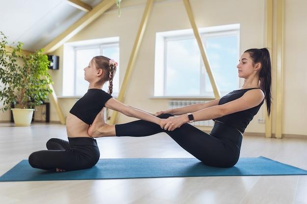 Treinadora jovem engajada no estúdio pessoalmente com uma garotinha ajudando a realizar um exercício para a flexibilidade da coluna, sentada em um tapete
