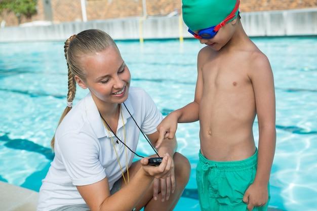 Treinadora mostrando cronômetro para menino