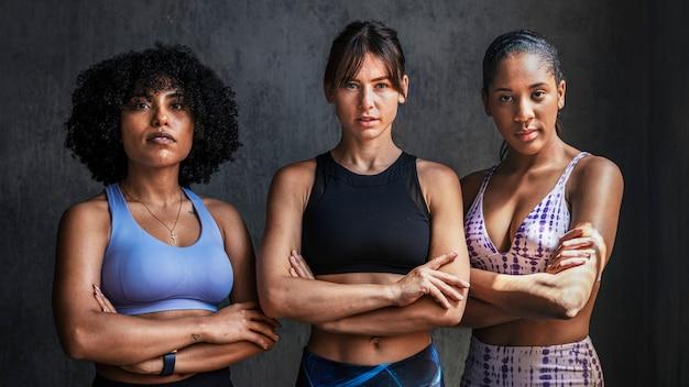Treinadoras pessoais esportivas femininas em pé com os braços cruzados