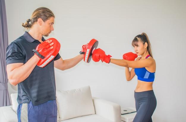 Treinadores de homens e mulheres estão ensinando como se exercitar na academia.
