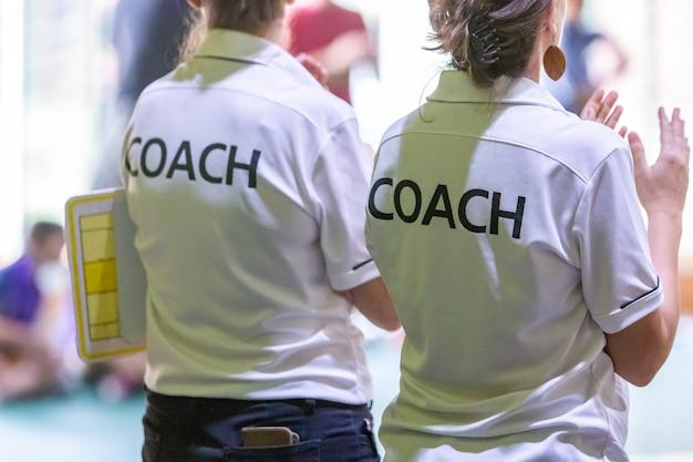 Treinadores fêmeas na camisa branca do treinador