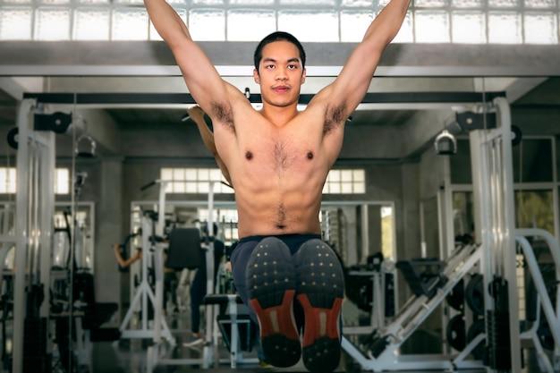 Treinamento asiático atlético forte do homem fisiculturista exercício músculo abdominal (l-sit) na barra no ginásio de fitness.