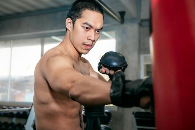 Treinamento asiático do pugilista do homem dos atletas em um saco de pancadas no gym da aptidão.