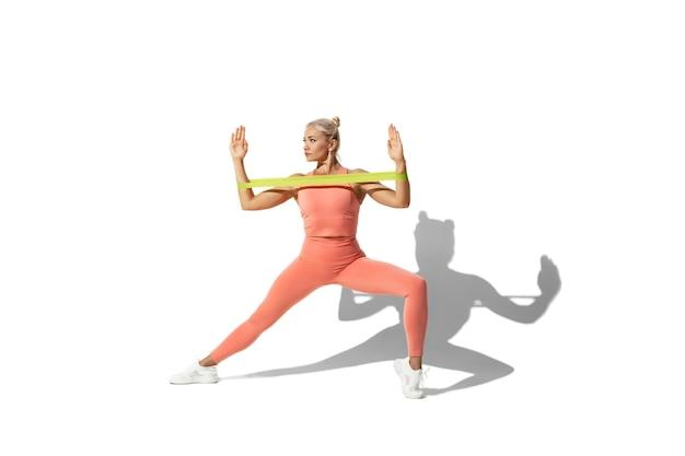 Treinamento. bela jovem atleta praticando na parede branca do estúdio, retrato com sombra.