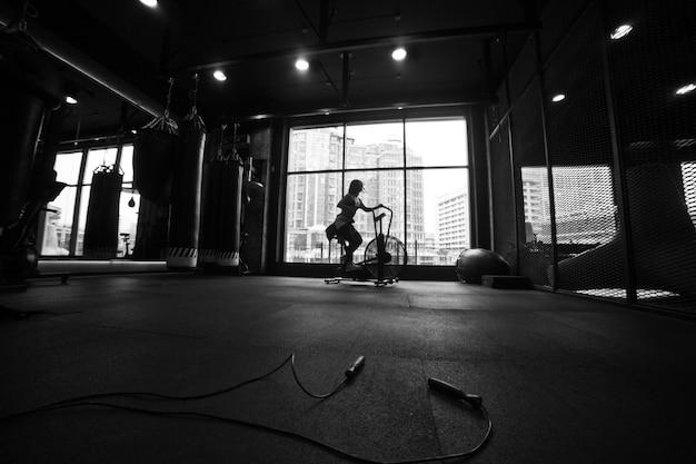 Treinamento cardíaco. silhueta preto e branco jovem desportiva usando bicicleta ergométrica no ginásio.