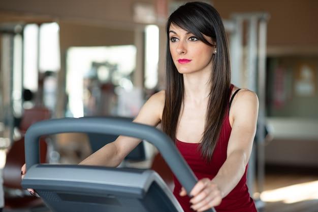 Treinamento cardiovascular de mulher em uma academia, fitness e conceito de corrida interna