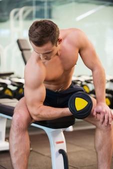 Treinamento com pesos. jovem confiante e musculoso treinando com halteres na academia