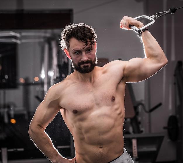 Treinamento cross fit na academia, homem musculoso está na academia, o conceito de esporte