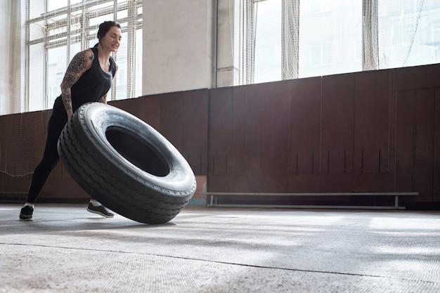 Treinamento cruzado. vista de baixo ângulo de uma atlética caucasiana tatuada, fortalecendo o corpo ao virar um pneu pesado em um pavilhão esportivo