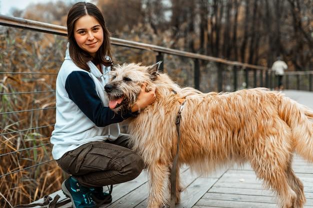 Treinamento de animais. uma garota voluntária anda com um cachorro de um abrigo de animais. menina com um cachorro no parque outono