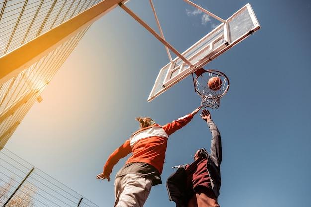 Treinamento de basquete. jogadores bem construídos tentando pegar a bola durante o treinamento de basquete