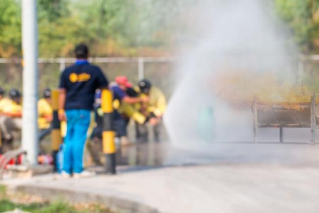 Treinamento de bombeiro de foto borrada, os funcionários treinamento anual combate a incêndios com gás e chamas
