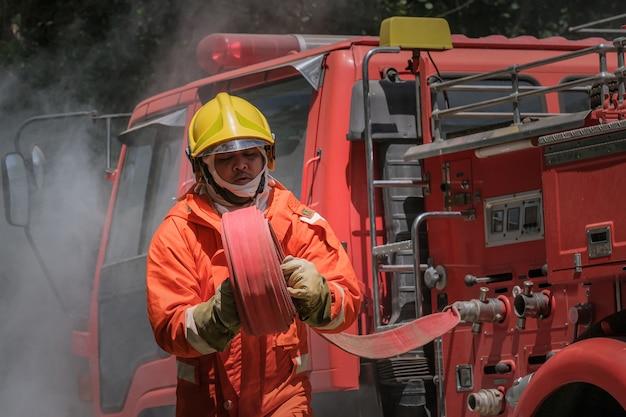 Treinamento de bombeiros, prática da equipe de combate ao fogo em situação de emergência.