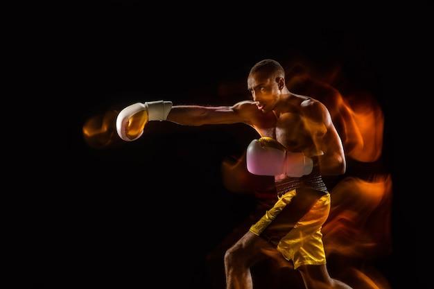 Treinamento de boxeador profissional isolado no preto