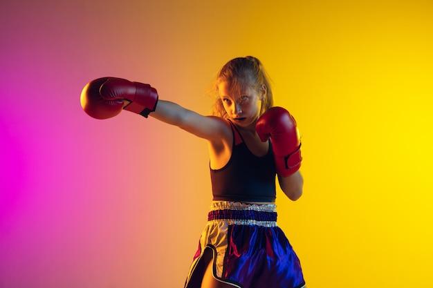 Treinamento de boxer chute feminino caucasiano pequeno em fundo gradiente na luz de neon, ativo e expressivo