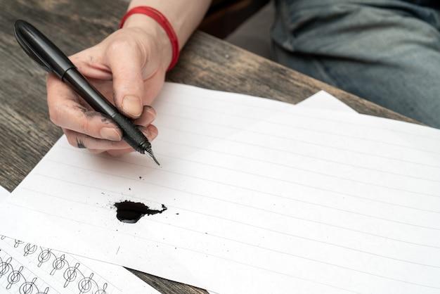 Treinamento de caligrafia. caneta-tinteiro nas mãos manchadas de tinta.