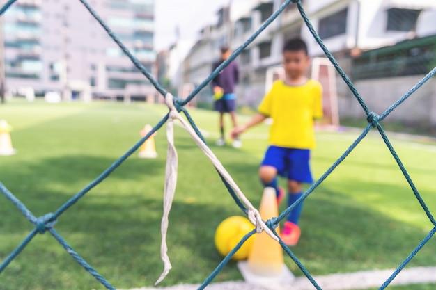 Treinamento de crianças de campo da academia de futebol desfocado