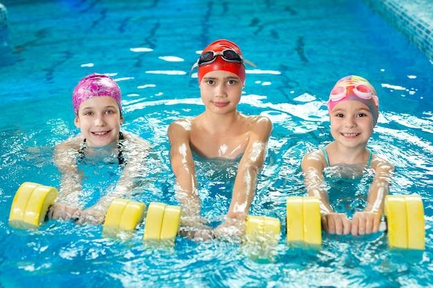 Treinamento de crianças na piscina com halteres, aulas de natação.