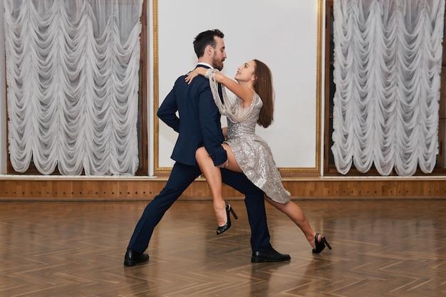 Treinamento de dança, homem e mulher com elementos de tango de prática de sentimento no salão de baile