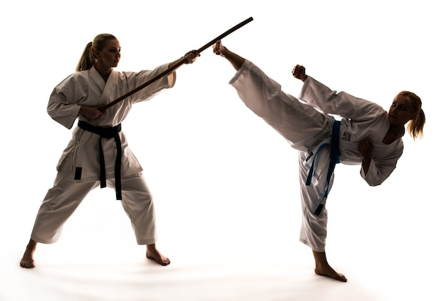 Treinamento de duas meninas em quimonos brancos usando equipamentos esportivos e carrinho de caratê. isolado em fundo branco