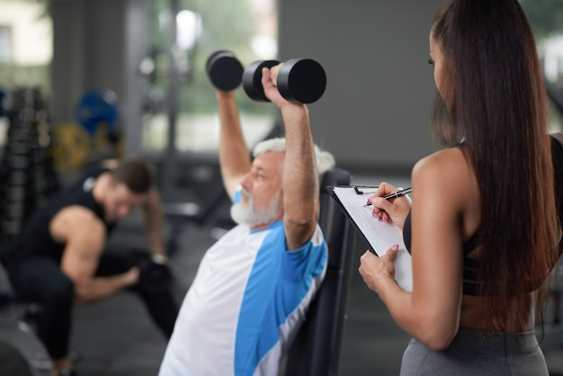 Treinamento de homem mais velho com mulher no ginásio.