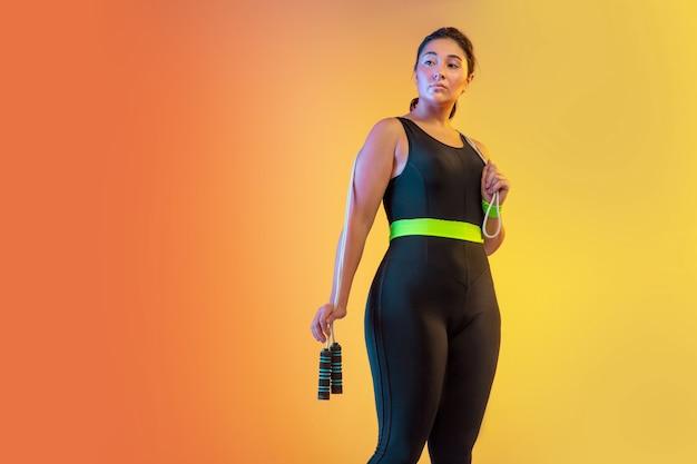 Treinamento de jovem modelo feminino caucasiano plus size em fundo laranja gradiente
