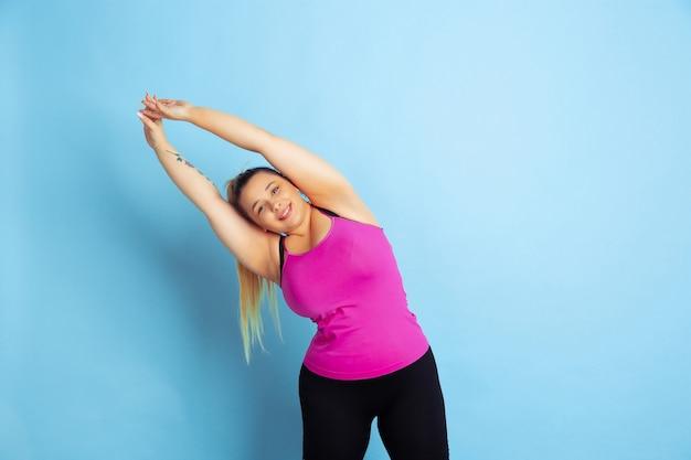 Treinamento de jovem modelo feminino caucasiano plus size sobre fundo azul