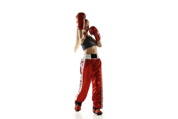 Treinamento de lutador de kickboxing feminino jovem isolado na parede branca. menina loira caucasiana em sportswear vermelho praticando artes marciais. conceito de esporte, estilo de vida saudável, movimento, ação, juventude.