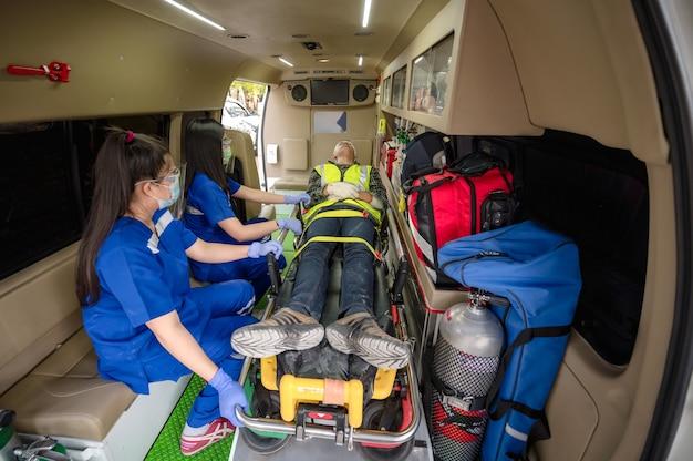 Treinamento de primeiros socorros para transferência de paciente, perda de sensibilidade ou perda de movimento normal. equipe paramédica transfere homem na maca da ambulância para o carro de emergência.