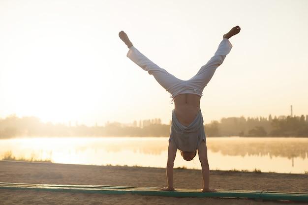 Treinamento de treino de capoeira atlético artista na praia ao nascer do sol