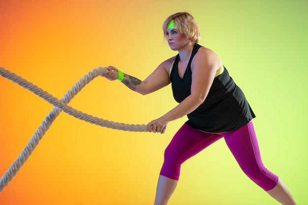 Treinamento do jovem modelo feminino caucasiano plus size em fundo gradiente laranja em luz de neon. fazer exercícios de treino com as cordas. conceito de esporte, estilo de vida saudável, corpo positivo, igualdade.