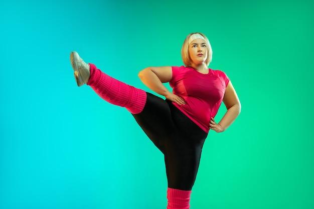 Treinamento do jovem modelo feminino caucasiano plus size na parede verde gradiente em luz de néon.