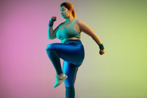Treinamento do jovem modelo feminino caucasiano plus size na parede verde roxo gradiente em neon. fazendo exercícios de alongamento. conceito de esporte, estilo de vida saudável, corpo positivo, igualdade.