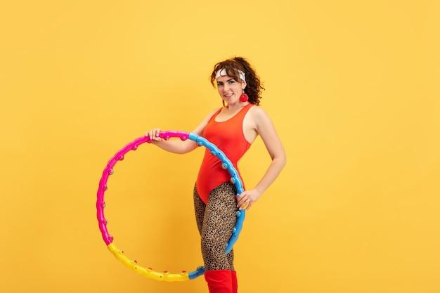 Treinamento do jovem modelo feminino caucasiano plus size sobre fundo amarelo. copyspace. conceito de esporte, estilo de vida saudável, corpo positivo, moda, estilo. mulher elegante praticando, posando com aro.