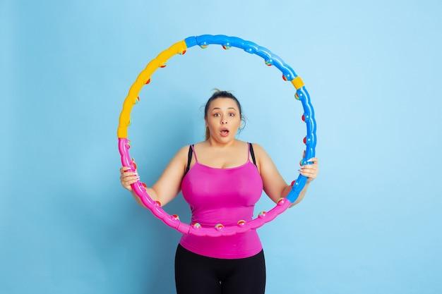 Treinamento do jovem modelo feminino caucasiano plus size sobre fundo azul. conceito de esporte, emoções humanas, expressão, estilo de vida saudável, corpo positivo, igualdade. espantado segurando o aro, chocado.