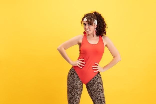 Treinamento do modelo feminino jovem caucasiano plus size na parede amarela. mulher elegante com roupas brilhantes. copyspace. conceito de esporte, estilo de vida saudável, corpo positivo, moda. posando flexível.