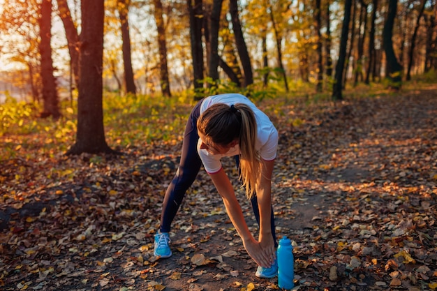 Treinamento e exercício no parque outono. mulher que estica as pernas que dobram-se ao ar livre. estilo de vida saudável e ativo