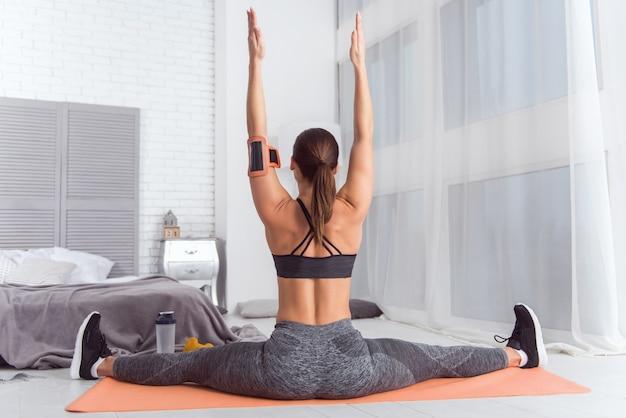 Treinamento em casa. mulher jovem e robusta, de cabelos escuros, vestindo roupas esportivas, fazendo exercícios enquanto está sentada no tapete em casa