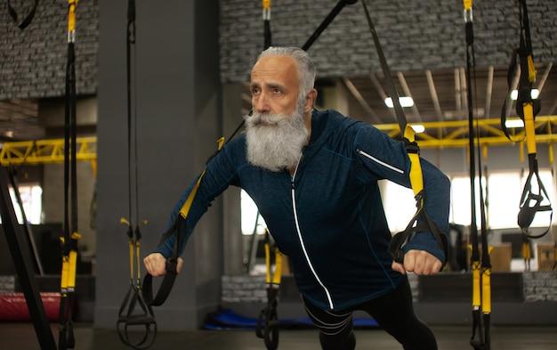 Treinamento esportista sênior barbudo com faixas de resistência trx no ginásio.