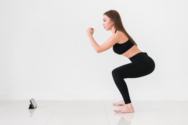 Treinamento esportivo on-line e mulher fazendo agachamentos