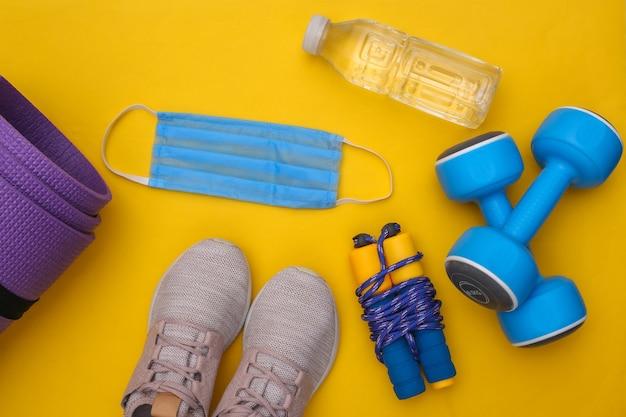 Treinamento físico durante o período covid-19. composição plana leiga de roupa de fitness, acessórios, máscara médica em fundo amarelo. conceito de estilo de vida saudável. vista do topo
