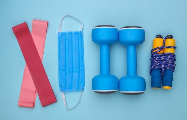 Treinamento físico durante o período covid-19. composição plana leiga de roupa de fitness, acessórios, máscara médica em fundo branco. conceito de estilo de vida saudável. vista do topo
