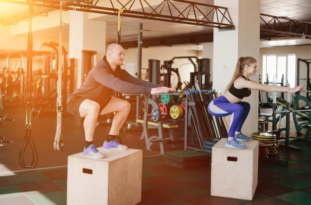 Treinamento funcional de casal. homem e mulher fitness pulam nas caixas de madeira na academia