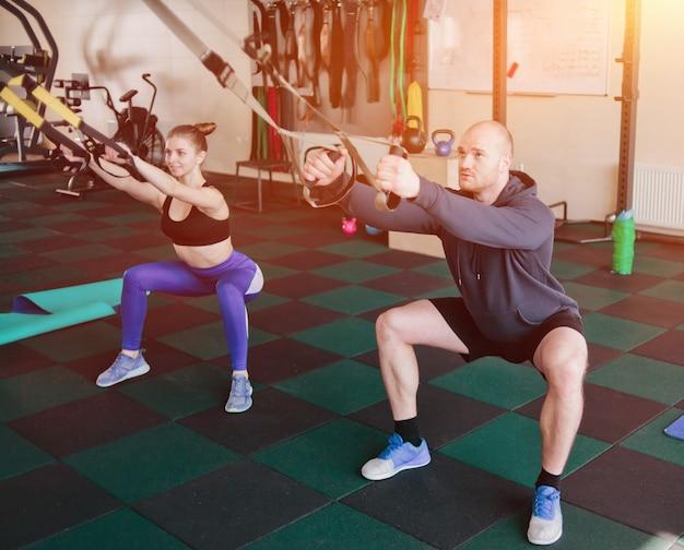 Treinamento funcional de casal. mulher e homem fazendo exercícios com alças de fitness no ginásio.