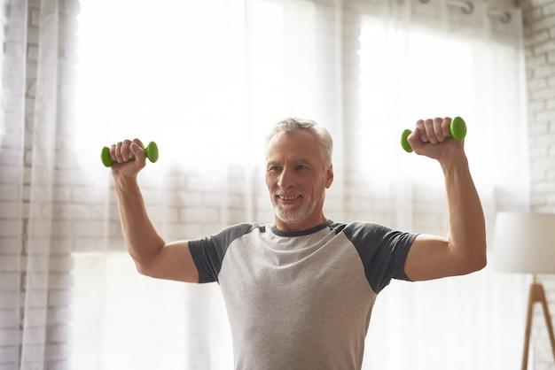 Treinamento idoso do bíceps do exercício do poder do homem em casa.