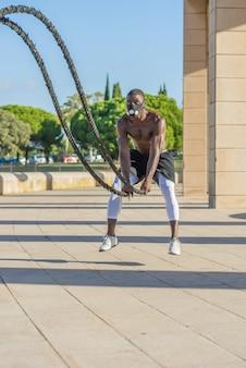 Treinamento muscular masculino com cordas de batalha e máscara de treinamento
