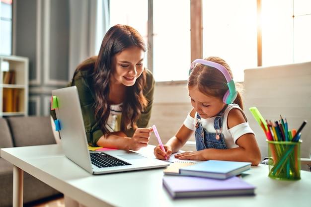Treinamento on-line. a mãe ajuda a filha com as aulas. aluna em fones de ouvido ouve uma lição em um laptop. escola em casa durante uma pandemia e quarentena.