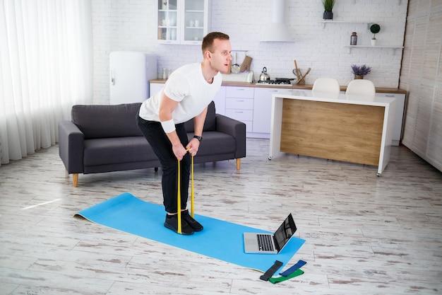 Treinamento on-line. jovem fazendo exercícios com elásticos de fitness com tutorial online em casa, espaço livre. praticando esportes em casa