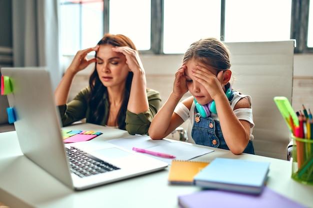 Treinamento on-line. lições muito difíceis. aluna com sua mãe escuta uma lição em um laptop. escola em casa durante uma pandemia e quarentena.