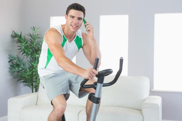 Treinamento sorridente de homem bonito em telefonia com bicicleta de exercício